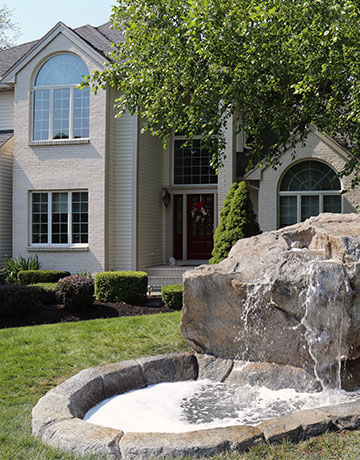 waterfall and pond in front of house