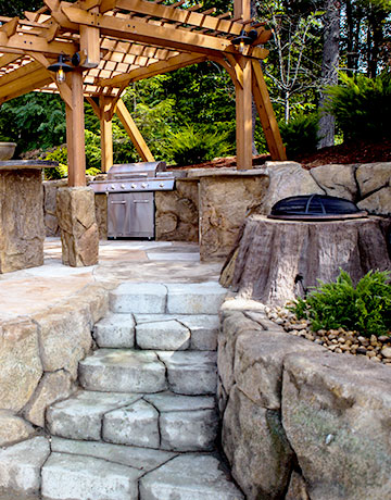 stone steps leading to fire pit and grill